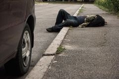 Drunk man lying outdoors. Stock Image