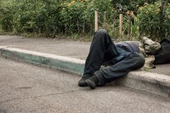 Drunk man lying on pavement. Unconscious person outdoors royalty free stock photos