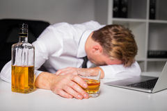 Drunk man at the office. Lying on table Royalty Free Stock Photo