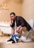 Drunk man with pants down sitting on toilet bowl Stock Photos
