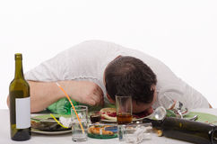 Drunk man puts his head in a plate Royalty Free Stock Photography
