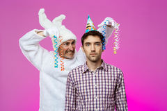 Drunk man and rabbit at birthday party over purple background. Royalty Free Stock Image