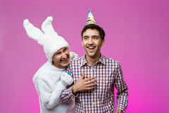 Drunk man and rabbit at birthday party over purple background. Royalty Free Stock Photos
