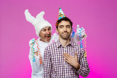 Drunk man and rabbit at birthday party over purple background. Royalty Free Stock Photography