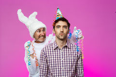 Drunk man and rabbit at birthday party over purple background. Royalty Free Stock Photo