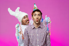 Drunk man and rabbit at birthday party over purple background. Stock Photography