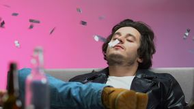 Drunk man relaxing on couch under falling confetti, listening to music at party. Stock footage stock footage