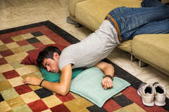 Drunk Man Resting on Couch with head on the Floor. Drunk Young Handsome Man Resting on Couch in the Living Room with Head on the Floor Stock Photo