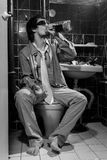 Drunk Man sits in a toile drink whiskey and smoking Royalty Free Stock Images