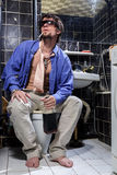 Drunk Man sits in a toilet with a bottle of whiskey Royalty Free Stock Photography