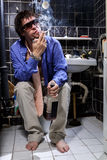 Drunk Man sits in a toilet with a bottle of whiskey and smoking Royalty Free Stock Image