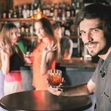 Drunk man sitting at bar, drinking cocktail, looking at girls Stock Photo