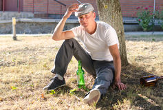Drunk man sitting at the base of a tree Royalty Free Stock Image