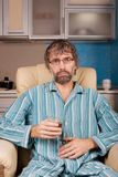 Drunk man sitting in chair with glass Stock Image