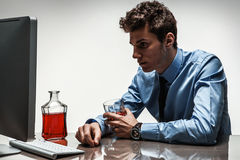 Drunk man sitting drunk at office holding glass Stock Photo
