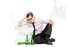Drunk man sitting by a toilet and holding white flag. Isolated on white background Royalty Free Stock Photos