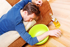 Drunk man sleeping on couch with whikey bottle and bowl Stock Photography