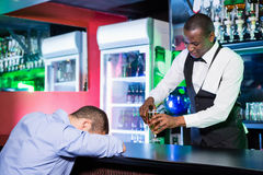 Drunk man sleeping with his head on bar counter Royalty Free Stock Photography