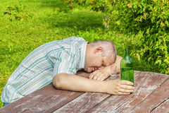 Drunk man sleeping near bottle of alcohol on table Royalty Free Stock Photos
