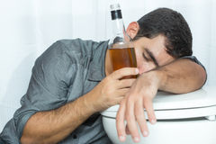 Drunk man sleeping on the toilet and holding a bottle Stock Photography