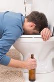 Drunk man sleeping on toilet and holding bottle. Stock Image