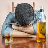 Drunk man sleeping with a whisky bottle on his table. Drunk man sleeping with a whisky bottle and a glass  on his table Stock Images