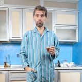 Drunk man standing in pajamas with glass Stock Image