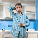 Drunk man standing in pajamas with glass Stock Photos