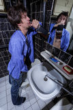 Drunk Man is standing in a toilet with a bottle of whiskey Royalty Free Stock Photo
