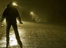 Drunk Man in Street. Drunk man silhouette, standing in road on foggy night, car headlights approaching, bottle in hand Royalty Free Stock Photography