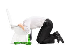 Drunk man throw up in a toilet. With empty beer bottles next to him isolated on white background royalty free stock photography