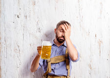 Drunk man in traditional bavarian clothes holding beer mugs Royalty Free Stock Photo