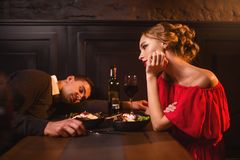 Drunk man sleeps at the table against woman Royalty Free Stock Photo