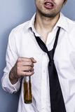 Drunk and messy businessman. Holding a bottle of hard liquor Royalty Free Stock Photo