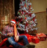 Drunk nerd in santa hat lying under the Christma tree with a lot Royalty Free Stock Photography