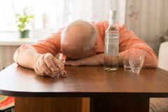 Drunk Old Man Leaning on the Table Holding a Glass Stock Photo