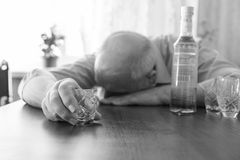 Drunk Old Man Sleeping on the Table. Close up Drunk Old Man Sleeping on the Table with Wine While Holding a Small Glass. Captured in Monochrome Royalty Free Stock Images