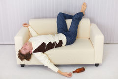 Drunk person funny sleeps on sofa Royalty Free Stock Image