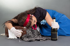 Drunk pinup girl with bottle of champagne lying on the suitcase Stock Photo