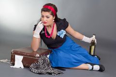 Drunk pinup girl with bottle of champagne Stock Photography