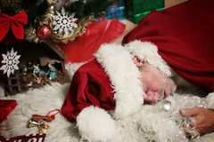 Drunk Santa Claus. Santa Claus sleeping under the Christmas tree with fake beard in hand. He got drunk in an office party or got tired during his gifts run Stock Images