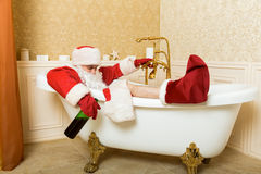Drunk Santa Claus with bottle sleeping in a bath. Funny drunk Santa Claus with alcohol bottle in hand sleeping in a bath. Christmas humor royalty free stock photos