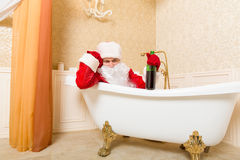 Drunk Santa Claus with bottle sleeping in a bath. Funny drunk Santa Claus with alcohol bottle in hand sleeping in a bath. Christmas humor royalty free stock images