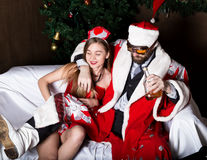 Drunk santa claus with female nurse woman in carnival costume drinking brandy. Drunk santa claus with female nurse women in carnival costume drinking brandy royalty free stock photo