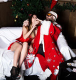 Drunk santa claus with female nurse woman in carnival costume drinking brandy. Drunk santa claus with female nurse women in carnival costume drinking brandy stock photos