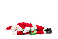 Drunk Santa Claus lying on the ground. With a few beer bottles around him on white background stock image