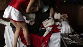 Drunk santa claus lying on sofa, female nurse sexy woman in carnival costume holding bullhorn, tries to wake him up stock video
