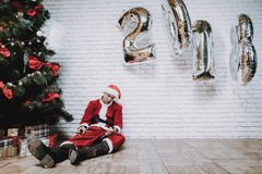 Drunk Santa Claus near New Year Tree after Party. Christmas Tree in Office. Celebrating of New Year. Red Costume. Man in Red Cap. Drank Man. Red Pants stock photo