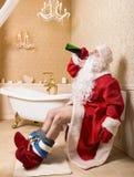 Drunk Santa Claus sitting on the toilet. Drunk Santa Claus with bottle of alcohol sitting on the toilet. Christmas humor stock images