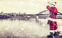 Drunk Santa Claus. Watching the city from river side Royalty Free Stock Image